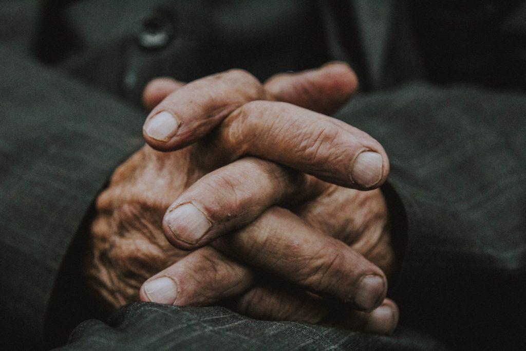 oude mannen handen in elkaar gevouwen