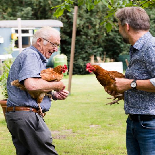 Bezoeker en verzorger houden kip vast bij dagbesteding de buitenhof tilburg