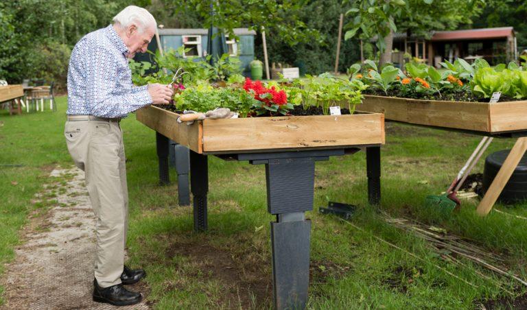 bezoeker de buitenhof verzorgt planten in plantenbak